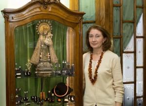 Loreto Pajarón ante una obra de la Virgen de los Desamparados realizada en el taller familiar. Foto de Manolo Guallart.