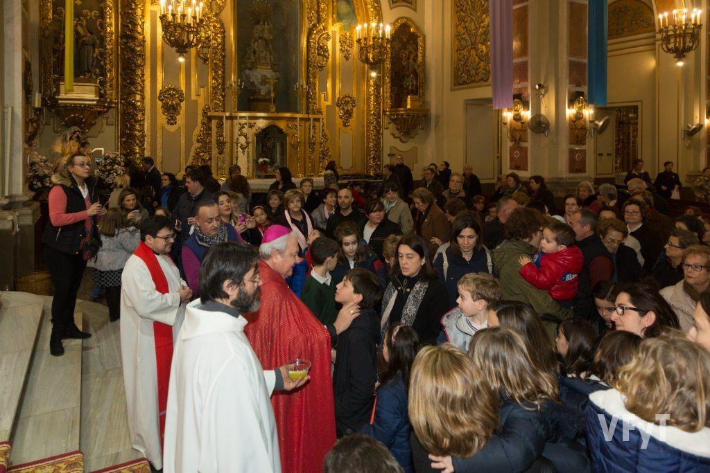 El obispo auxiliar de Valencia, Javier Salinas, en la imposición de aceite sobre la garganta de los niños. Foto de Manolo Guallart.
