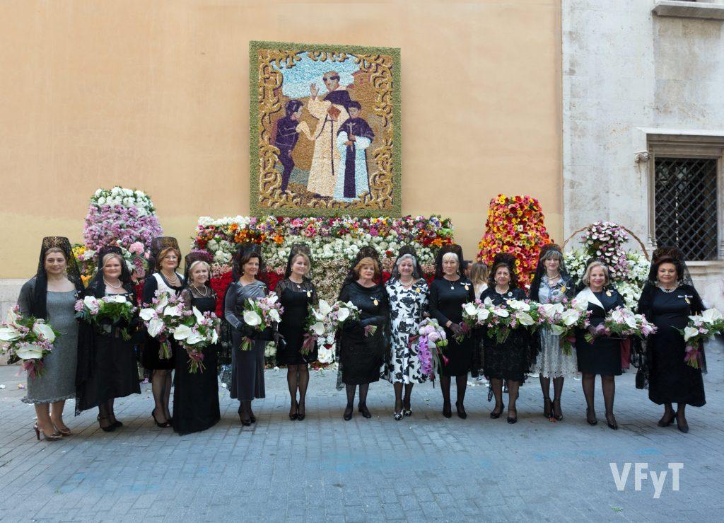 Honorable Clavariesas de años anteriores acompañan a Carmela Morell en la Ofrenda al santo. En la imagen, con el tapiz en la calle del Mar, en la entrada de la Casa Natalicia.