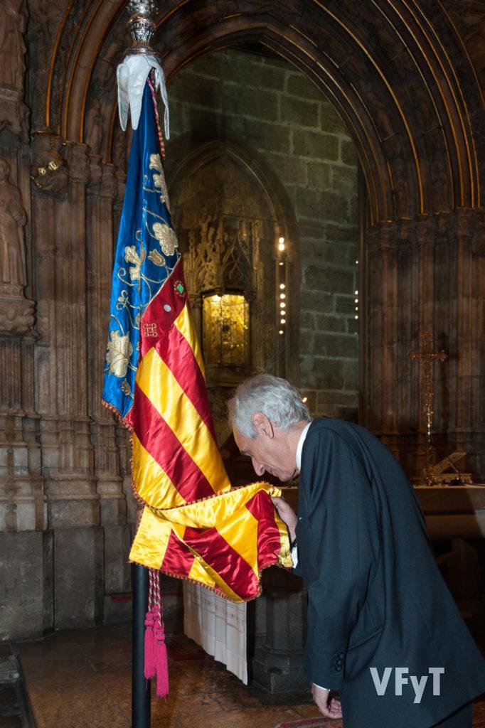 Miquel Ramón, Lloctinent General del Centenar de la Ploma, besa la Real Senyera ante el Santo Cáliz.