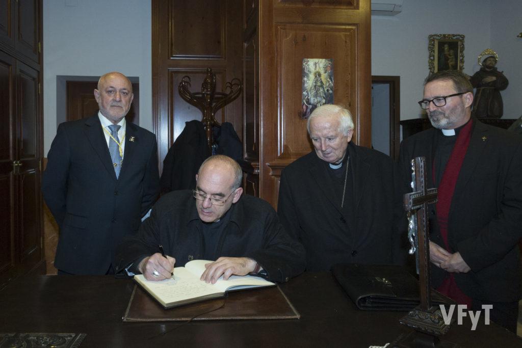 El obispo Ros firma en el Libro de Oro de la Junat Mayor de la Semana Santa. Foto de Manolo Guallart.
